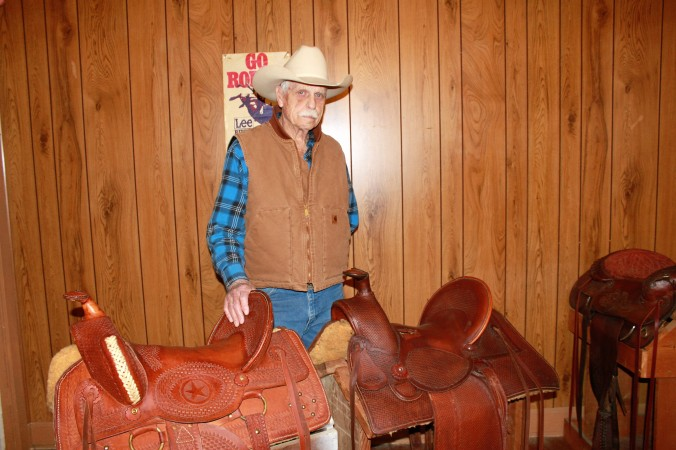 Jack Short, who attended saddle-making school in South Dakota, is shown with two of the saddles he restored by hand, both for range horses, which require a higher horn. Shown left is a 1900 era saddle with the high horn made from leather he cut and stamped with a saddle stamp and stitched by hand with brass-covered stirrups. Shown right is an 1880 era saddle with a slick fork, covered dees, high horn, high back, slotted seat and brass-covered stirrups. Modern saddles are broader with lower horns.